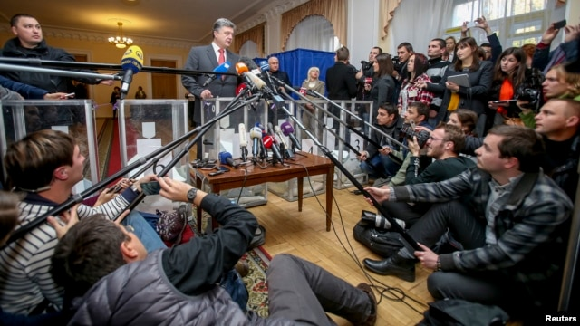 Ukrainian President Petro Poroshenko (center) talks to the media as he visits a polling station during parliamentary elections in Kyiv on October 26.