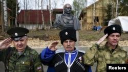 «Казаки» отдают честь во время церемонии открытия бюста президента России Владимира Путина в Ленинградской области России