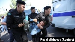 Қозоғистон полицияси митинг иштирокчисини олиб кетмоқда. Алмати шаҳри, 2019, 21 сентябрь.