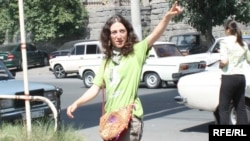 "Armenia -- Mariam Sukhudian, a civic activist charged with ""false deninciation,"" greets supporters as she heads to a police station in Yerevan for interrogation on August 19, 2009."