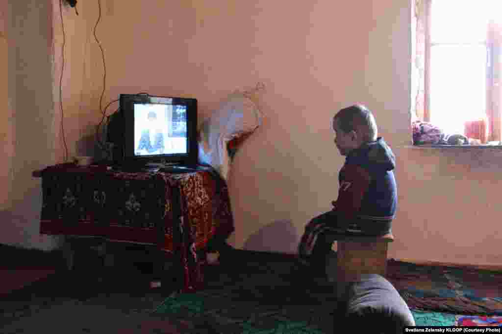 Four-year-old Kurbanbek is the youngest resident of the half-abandoned village. Here, he watches local Tajik television.