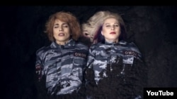 The single-take video shows group members Nadezhda Tolokonnikova and Maria Alyokhina clad in Russian riot-police uniforms and being buried alive.