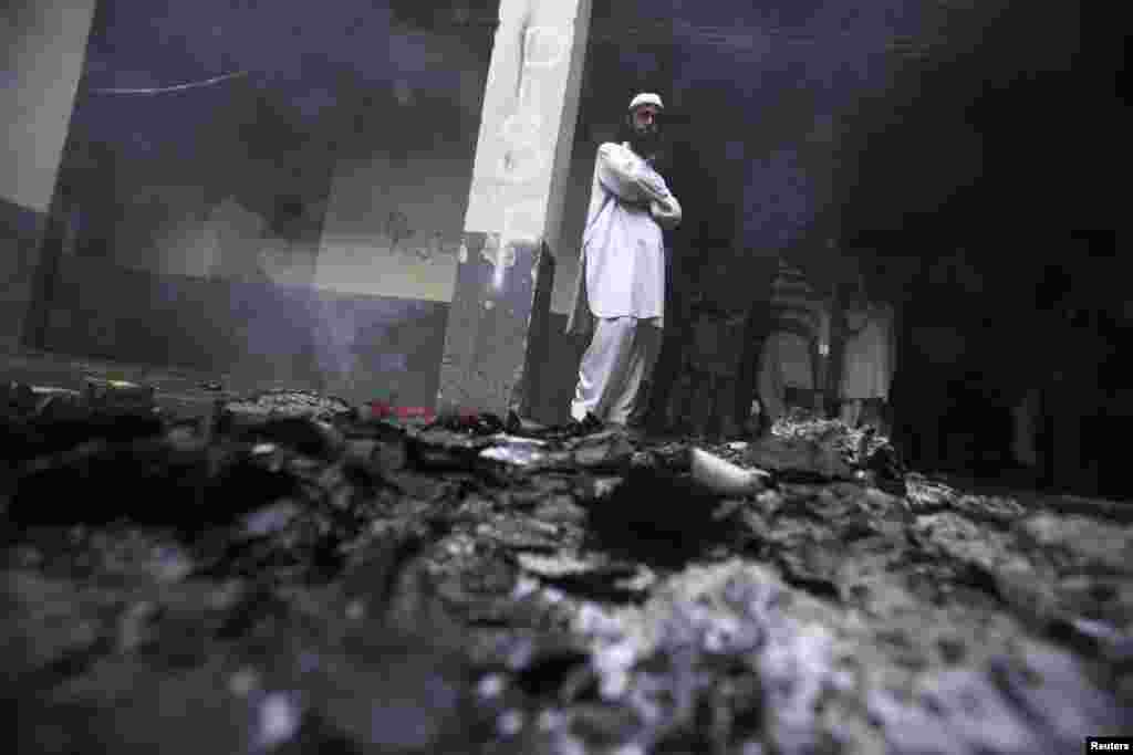 A student stands near ashes in a hostel room after it was torched during a clash between two student groups  at Peshawar University on Valentine's Day. (Reuters/Fayaz Aziz)