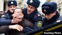Arxiv fotosu: Bakıda müxalifətin etiraz aksiyasında saxlanan fəallardan birinin şüar qırşqırmasına mane olmağa çalışan polis əməkdaşları, 12 mart 2011