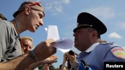 An Interior Ministry officer speaks to a participant in an LGBT rally in St. Petersburg on August 12.
