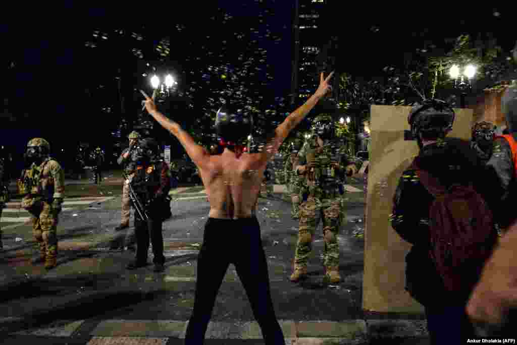 "A topless protestor (C) gestures in front of federal police personnel in Portland, Oregon early July 26, 2020, as protests continue across the United States following the death in Minneapolis of unarmed African-American George Floyd. - Police and federal agents fired tear gas and forcefully dispersed protesters in the US city of Portland, amid President Donald Trump's heavily-criticized ""surge"" of security forces to major cities. The city, the biggest in the state of Oregon, has seen nightly protests against racism and police brutality for nearly two months, initially sparked by the death of unarmed African American George Floyd at the hands of police in Minnesota (Photo by Ankur Dholakia / AFP)"