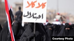 "Female supporters of Muqtada al-Sadr march in Baghdad in May, with one holding a sign saying, ""No, No to the Occupation!"""