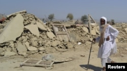 An earthquake survivor walks past the rubble of a mud-brick house in Awaran district.