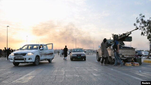 Fighters of the Islamic State of Iraq and the Levant (ISIL) stand guard at a checkpoint in the northern Iraqi city of Mosul on June 11.