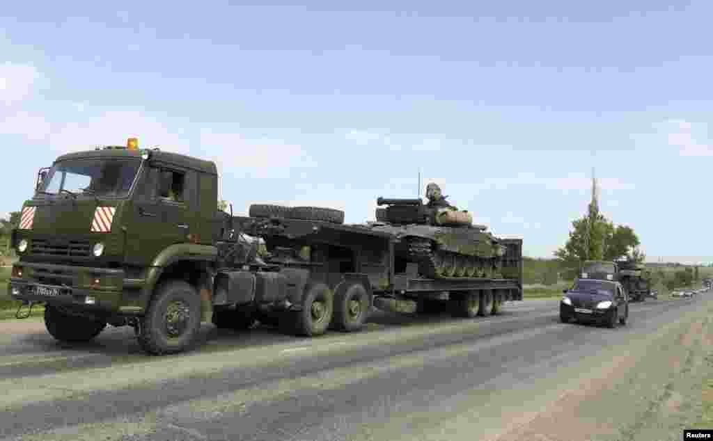 Вантажівки перевозять танки по трасі на російсько-українському кордоні. За три місяці кількість техніки на полігоні Кузьмінський в Ростовській області збільшилася приблизно в три рази