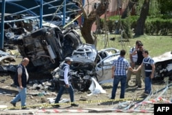 Rescue workers and police inspect the blast scene after a car bomb attack on a police station in the eastern Turkish city of Elazig on August 18.