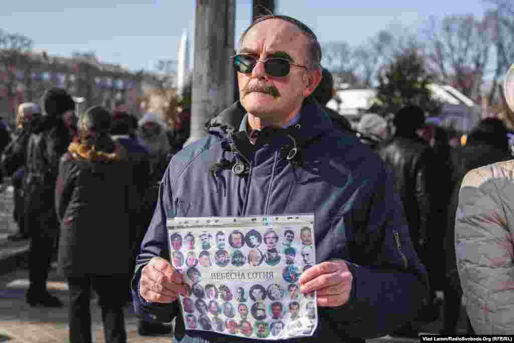 Чоловік з портретами загиблих під час Революції