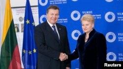 Ще 28 листопада 2013 року у Вільнюсі президент Литви Даля Ґрібаускайте як господар саміту «Східного партнерства» тиснула руку своєму українському колезі Януковичу