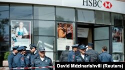 Armenian police officers stand guard after a fatal shooting incident at a branch of HSBC Bank in Yerevan on May 3.