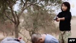"""Казакстандык аты бдулла деген бала Орусиянын чалгындоо кызматынын тыңчысы деп айыпталган эки эркекти тапанчадан атып өлтүрүүдө. Видеосүрөттү 2015-жылы 15-январда ИМдин """"ал-Хаят"""" медиа борбору жарыялаган."""