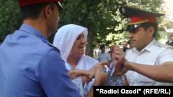 Сотрудники милиции задерживают Гульчехру Шодмонову, мать подозреваемого в нападении на иностранных велотуристов. Душанбе, 7 сентября 2018 года.