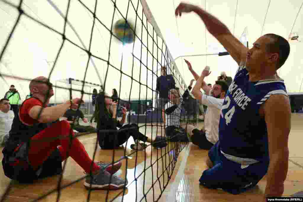 Учасники американської й української команд грають у сидячий волейбол