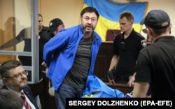 Тодішній керівник «РИА Новости Украина» Кирило Вишинський (посередині), якого в Україні звинуватили, зокрема, у державній зраді та незаконному зберіганні зброї. Київ, 19 липня 2019 року