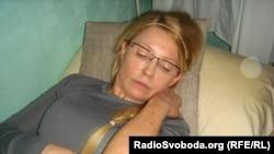 Юлия Тимошенко Кеше хокукларының югары шурасы вәкиле Нина Карпачевага үзенең кара янган кулларын күрсәтә