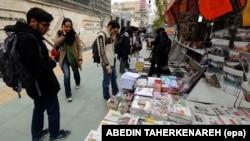 Tineri iranieni la un chioșc de presă pe o stradă din Teheran