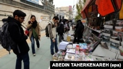 Iranians look at newspapers displayed on the ground outside a kiosk in a street of Tehran. File photo