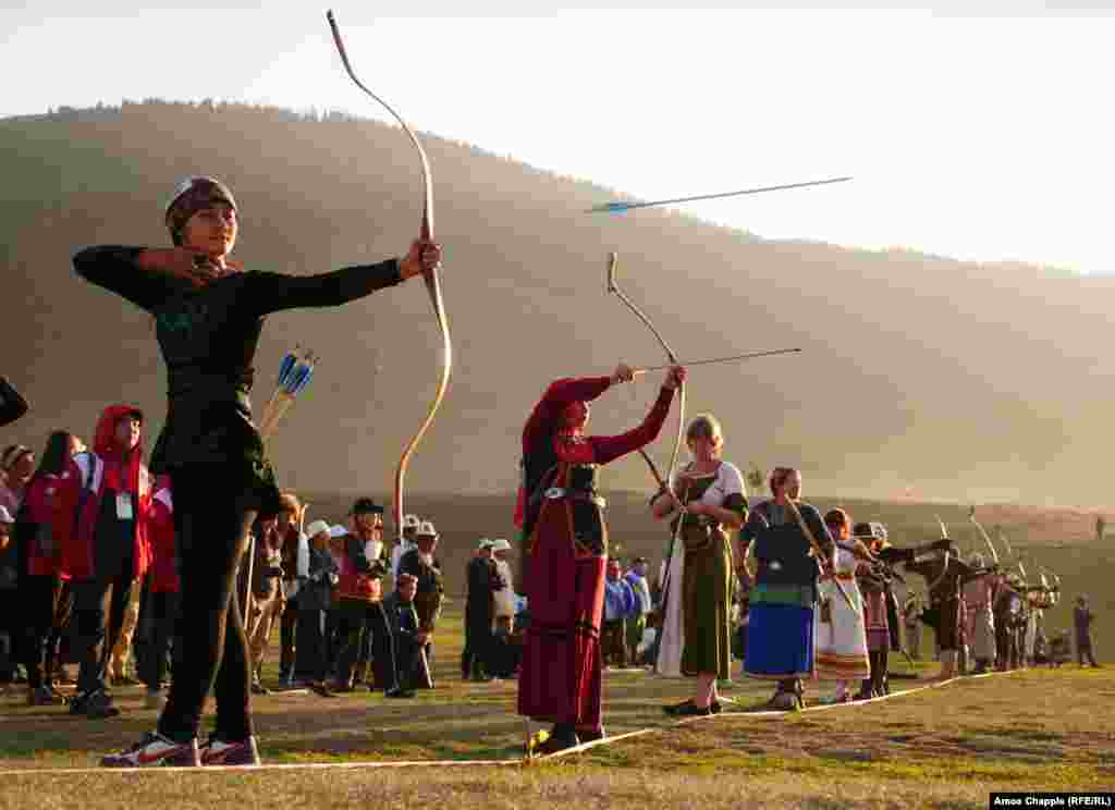 An arrow flies from the bow of Ayana Rustam (left), from Kyrgyzstan, alongside other competitors during one of the standing archery events.