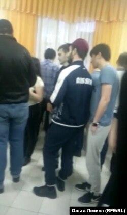 Cкриншот видео с парнями, обступившими Ольгу (в центре в белом)
