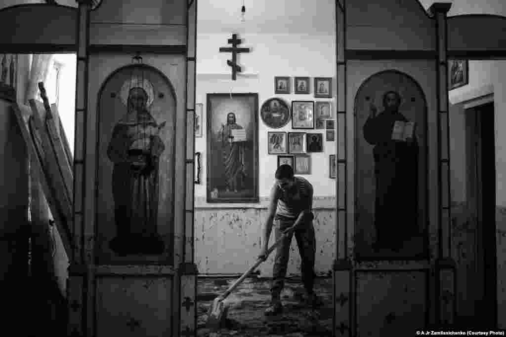 Photographer Alexander Zemlianichenko Jr. of Russia was selected for this image of a soldier cleaning mud and silt from inside a church in the village of Nizhnebakanskaya near Krymsk, Russia.