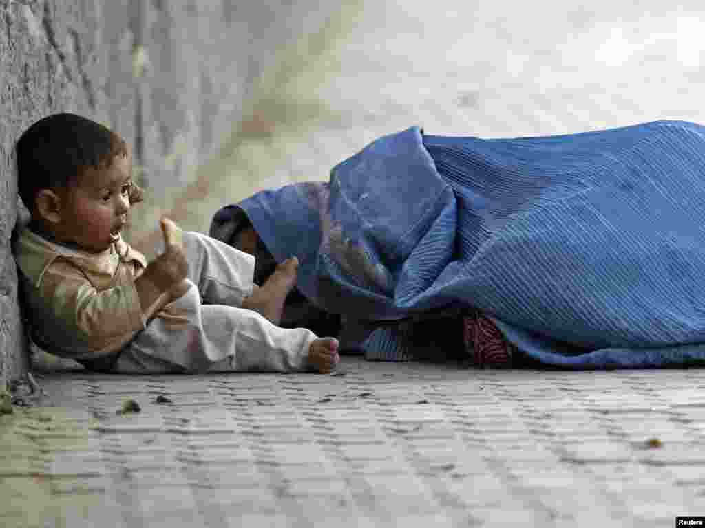 An Afghan woman sleeps by the roadside as her child nibbles a piece of bread outside a mosque during Ramadan in Kabul on September 8. Photo by Fayaz Kabli for Reuters