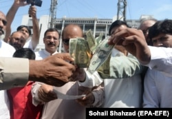 People burn U.S. dollars in protest of the deteriorating economy in Islamabad in May 2019.