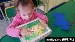 """Ребенок играет в развивающие игры на планшетнике в инклюзивном центре развития """"Капитошка"""". Темиртау, 26 марта 2015 года."""