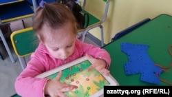 """Ребенок играет в развивающие игры в центре """"Капитошка"""". Темиртау, 26 марта 2015 года."""