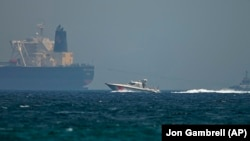 An Emirati coast guard vessel passes an oil tanker off the coast of Fujairah, May 13, 2019