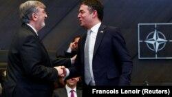 Yunanıstanın NATO-dakı səfiri Spiros Lambridis (solda) Makedoniya xarici işlər naziri Nikola Dimitrovu təbrik edir