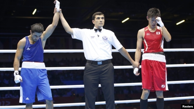 Turkmen referee Ishanguly Meretnyyazov (center) was criticized for allowing Azerbaijan's Magomed Abdulhamidov (left) too much time to recover in his bout with Japan's Satoshi Shimizu (right).
