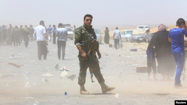 A member of Iraqi Kurdish security forces stands guard as families fleeing violence in the city of Mosul wait at a checkpoint in outskirts of Irbil on June 10.