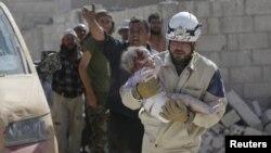 Спасатель несет ребенка, раненного, как сообщается, при разрушениях от авиаудара. Окрестности города Идлиб в Сирии, 20 октября 2015 года.