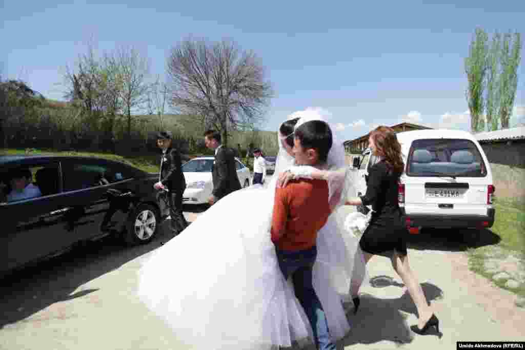 Старший брат Аякоз на руках доносит сестру до машины жениха.
