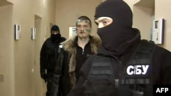 Adam Osmayev walks under escort of masked agents of the Ukrainian Security Service in Odesa.