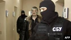 Adam Osmayev walks under escort of masked agents of the Ukrainian Security Service in Odesa.