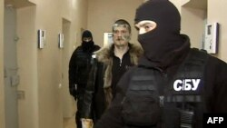 A Russian Channel 1 screen grab shows a man identified as Adam Osmayev (center), one of the suspects alleged to have conspired to kill Vladimir Putin, being escorted by masked agents of the Ukrainian Security Service in Odesa.