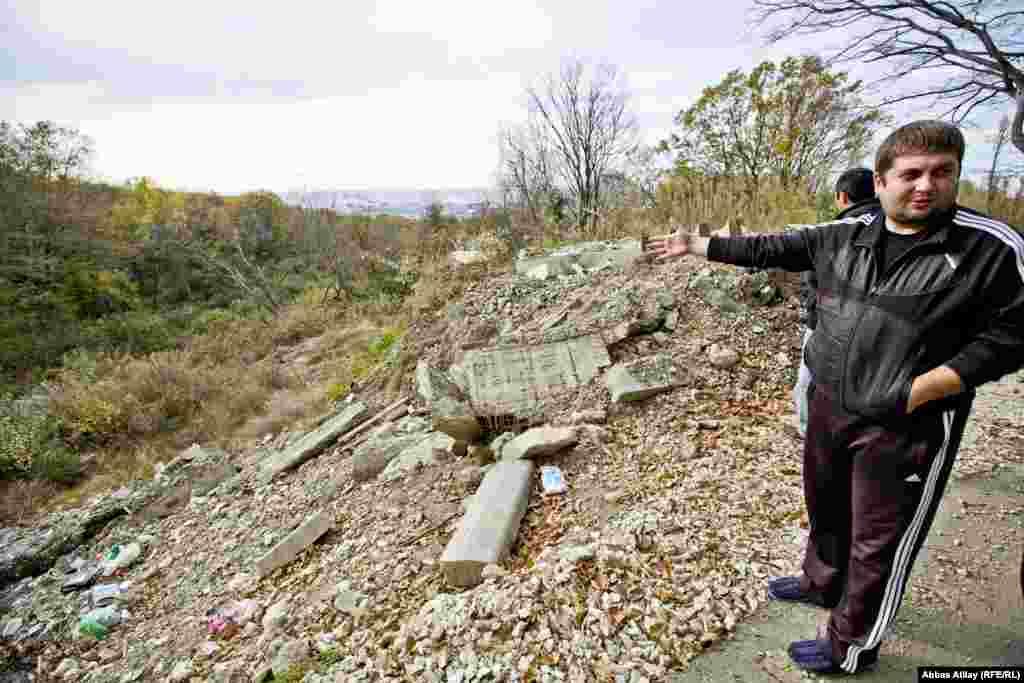 27-річний Дмитро Абжан показує місце вище від його будинку, де вантажівки з олімпійського будівництва звалювали сміття, котре й виклало зсув.