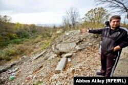 Дмитрий Абжан үй жанындағы қоқысты көрсетіп тұр.