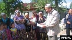 Чек кыштагынын тургуну Манап Божоев кыргыз президентине жазылган кайрылуу менен айылдаштарын тааныштырууда.