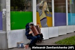 A woman plays accordion for money just outside Moscow in May.