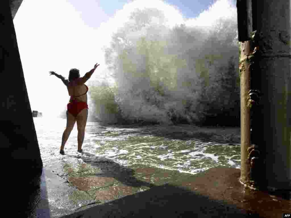 Russia -- A woman stands in front of a large wave on the beach of the Black sea resort of Sochi, 04Oct2010 - A woman stands in front of a large wave on the beach of the Black sea resort of Sochi on October 4. Photo by Mikhail Mordasov for AFP