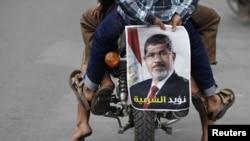 Демонстранты едут на мотоцикле с портретом смещенного президента Египта Мохаммед Мурси. Сана, 8 июля 2013 года.