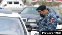 ARMENIA -- A police officer checks a driver's documents during a coronavirus lockdown as a preventive measure against coronavirus disease, in Yerevan, April 2, 2020