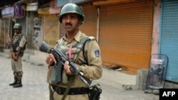 Indian paramilitary troopers stand guard during a curfew Srinagar, the summer capital of Kashmir.