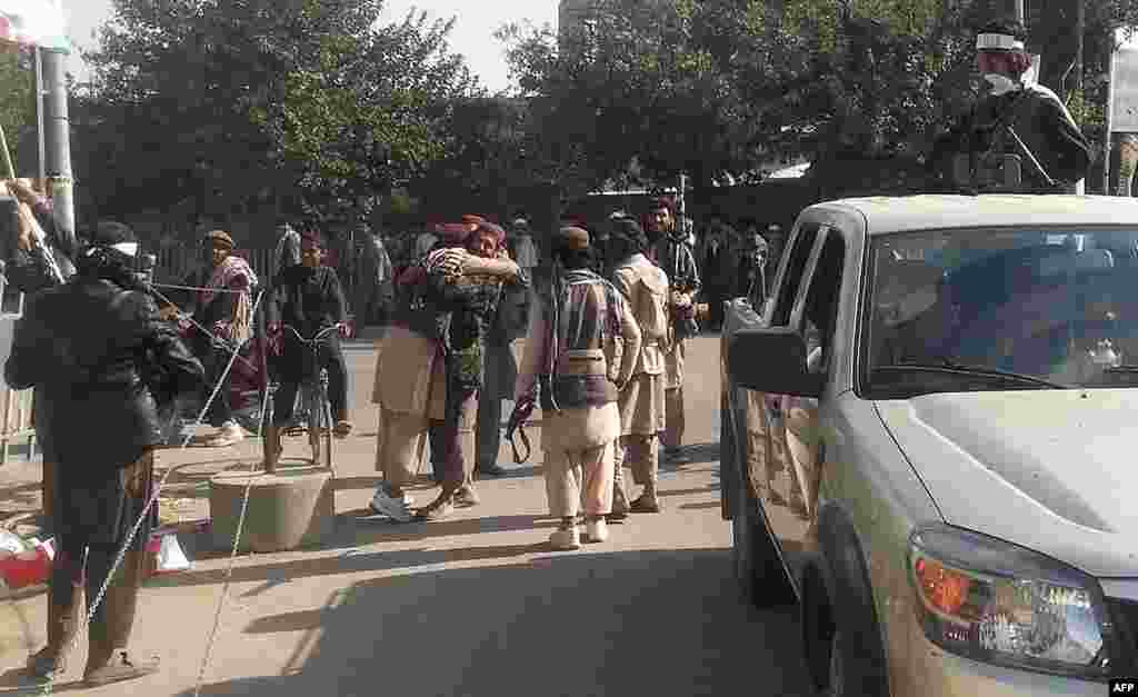 Taliban fighters hug each other after they overran the strategic northern city of Kunduz.